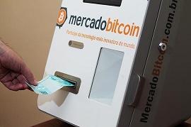 Imagem mostra alguém colocando dinheiro em um caixa eletrônico de bitcoins