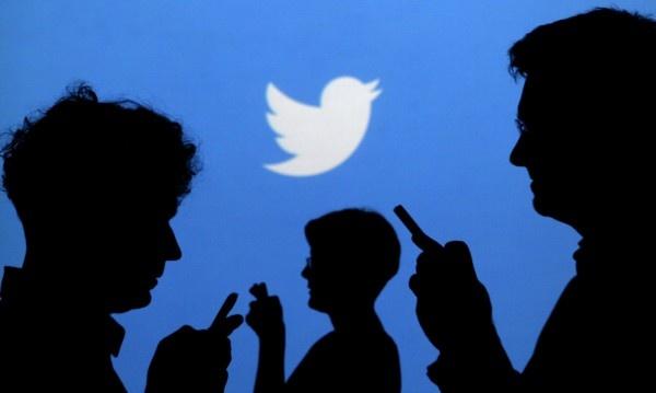 Pessoas no celular com a logo do twitter atrás