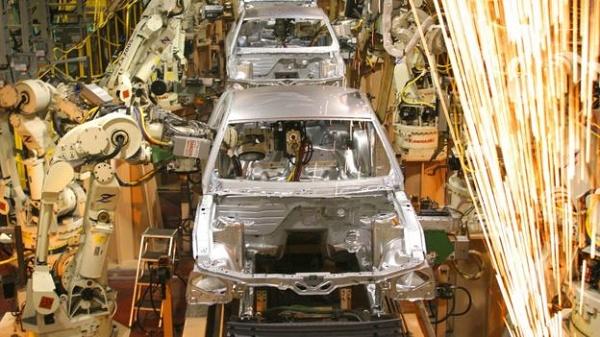 Robôs construindo carros