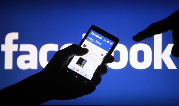 logo do facebook com uma mão segurando um celular