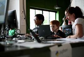 Professora ensinando duas crianças a mexerem no computador