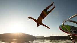 Homem mergulhando no mar a partir de um barca