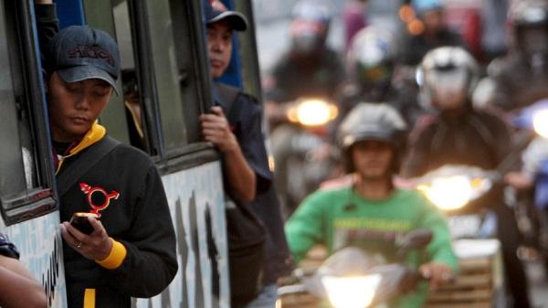 Menino na porta do ônibus olhando seu smartphone