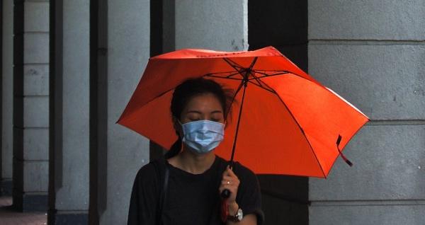 Moça com guarda-chuva e  máscara de proteção contra vírus