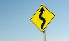 Uma placa de sinalização com uma seta e algumas curvas